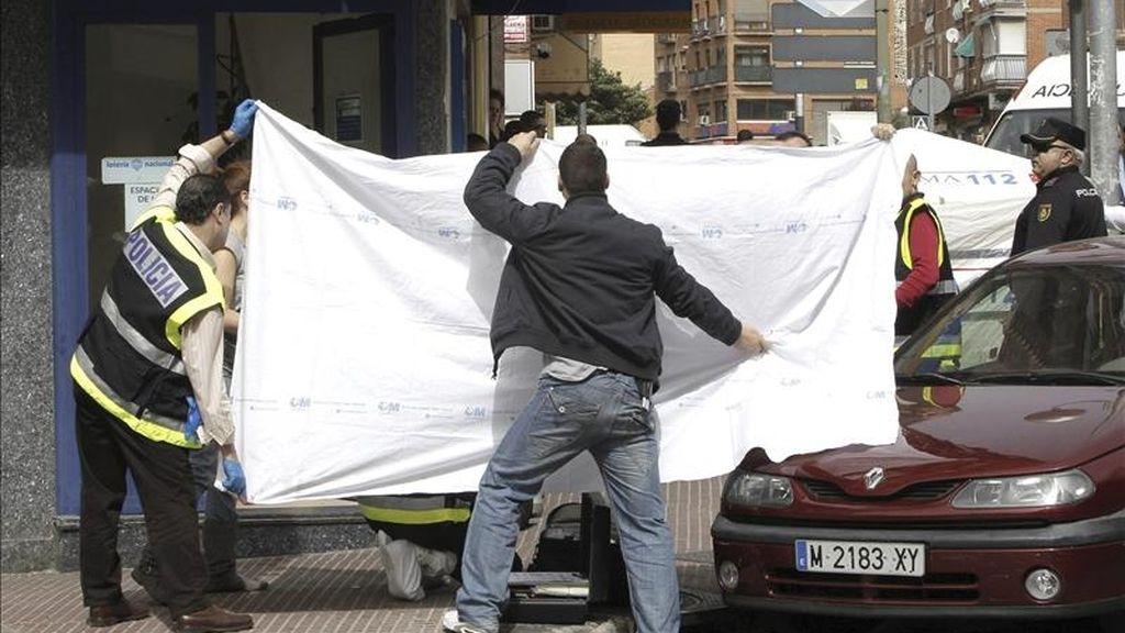 Varios agentes de la policía junto a la Administración de Loterías de la calle Juan XXIII de Móstoles (Madrid) donde hoy una trabajadora de 34 años, ha fallecido tras recibir varias puñaladas por parte de un individuo que ha asaltado el local y que ha huido tras cometer la agresión. EFE