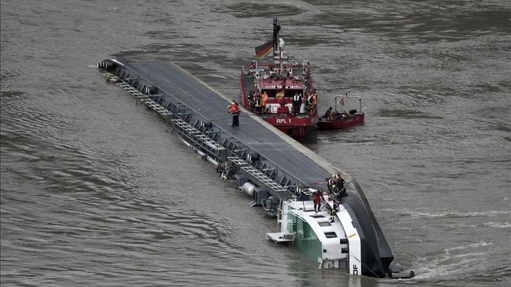 Una embarcación de los bomberos alemanes inspecciona la situación en la que se encuentra el barco cargado con 2.400 toneladas de ácido sulfúrico naugragado en el Rin, a su paso por la localidad alemana de Bingen. EFE