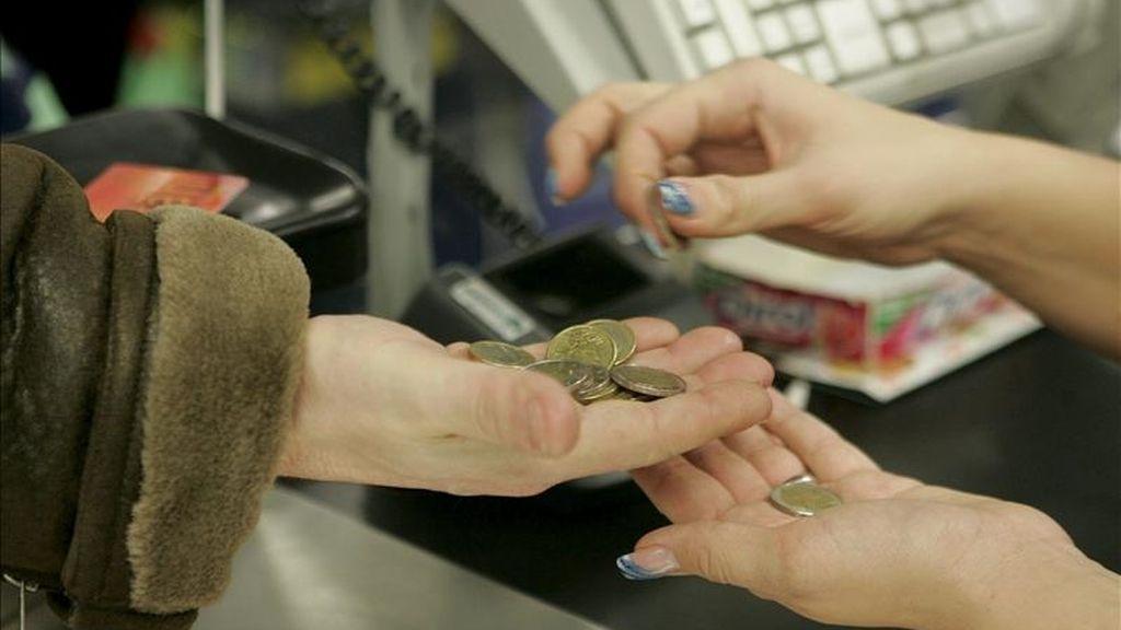En la imagen, una cajera ayuda a un cliente a contar las monedas en un supermercado. EFE/Archivo