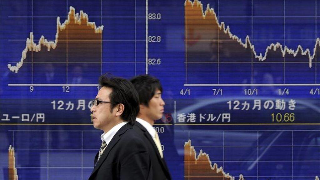 Dos ejecutivos japoneses caminan frente a una pantalla que muestra los valores de la Bolsa de Tokio (Japón). EFE/Archivo