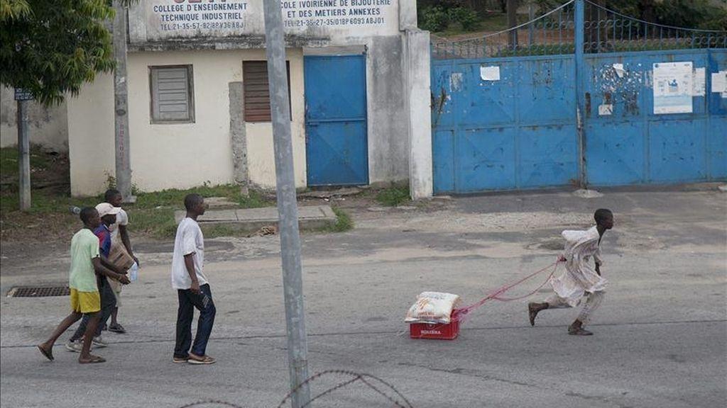 Marfileños transportando comida en una calle de Abiyán, Costa de Marfil. EFE