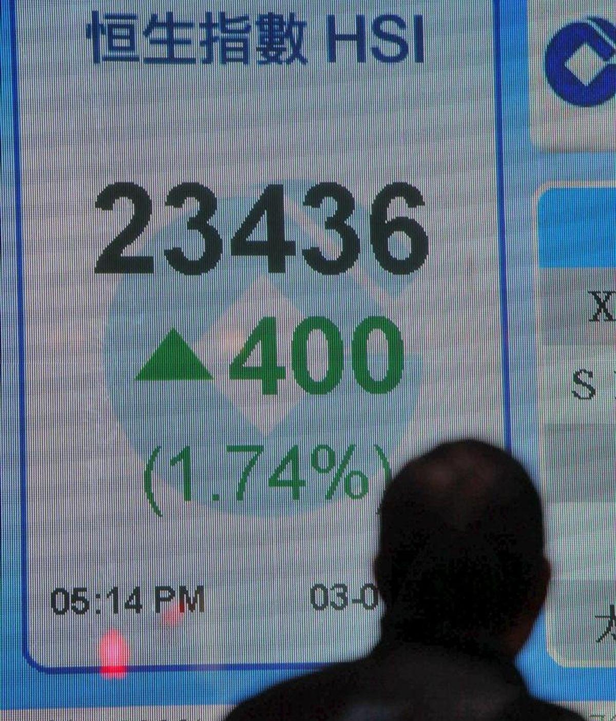 Un hombre camina junto a una pantalla informativa de los valores del índice Hang Seng en un banco en Hong Kong. EFE/Archivo