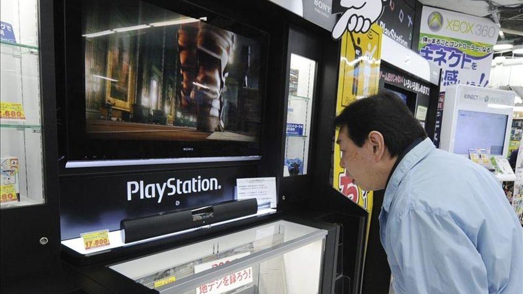 Un hombre se detiene hoy ante una consola Play Station en una tienda de electrodomésticos en el centro de Tokio (Japón). Sony ha contratado a una agencia de seguridad externa para que investigue el posible robo de información privada de 77 millones de cuentas de los servicios en red de PlayStation (PSN). EFE