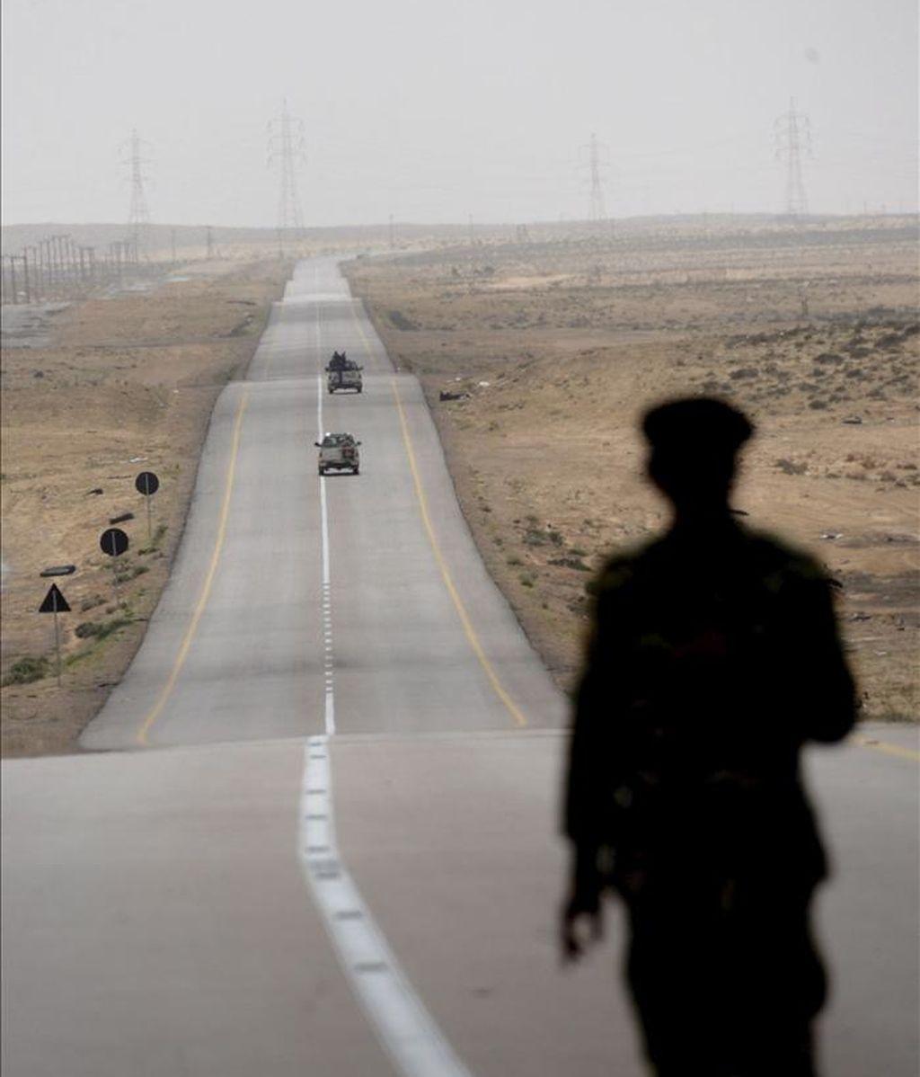 Un soldado rebelde libio observa una carretera cerca de la línea de combate entre Ajdabiya y Brega, en Libia. Los rebeldes libios que intentaban retomar el noroeste del puerto petrolero de Brega fueron replegados hacia la ciudad de Ajdabiya por las fuerzas leales a Gadafi. EFE