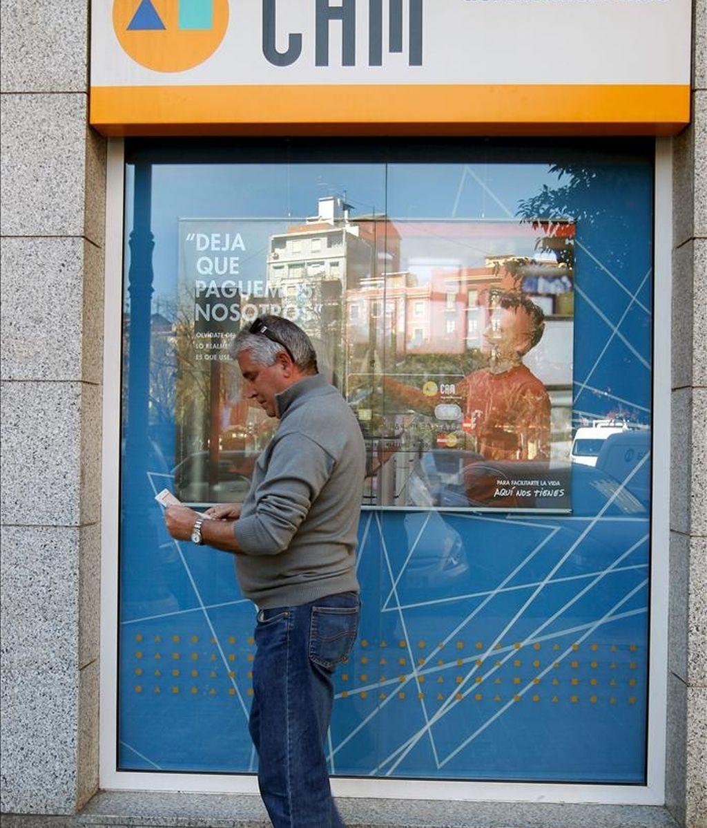 En la imagen, un usuario de la CAM consulta su libreta ante una de las oficinas de la caja de ahorros. EFE/Archivo