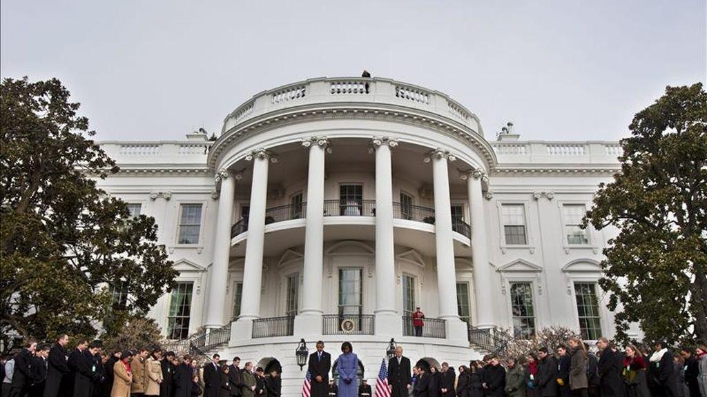 El presidente de Estados Unidos, Barack Obama, su esposa Michelle Obama (c) y empleados de la Casa Blanca guardan un minuto de silencio, en la Casa Balanca de Washington DC, para condenar el tiroteo del sábado en Tucson, Arizona. EFE