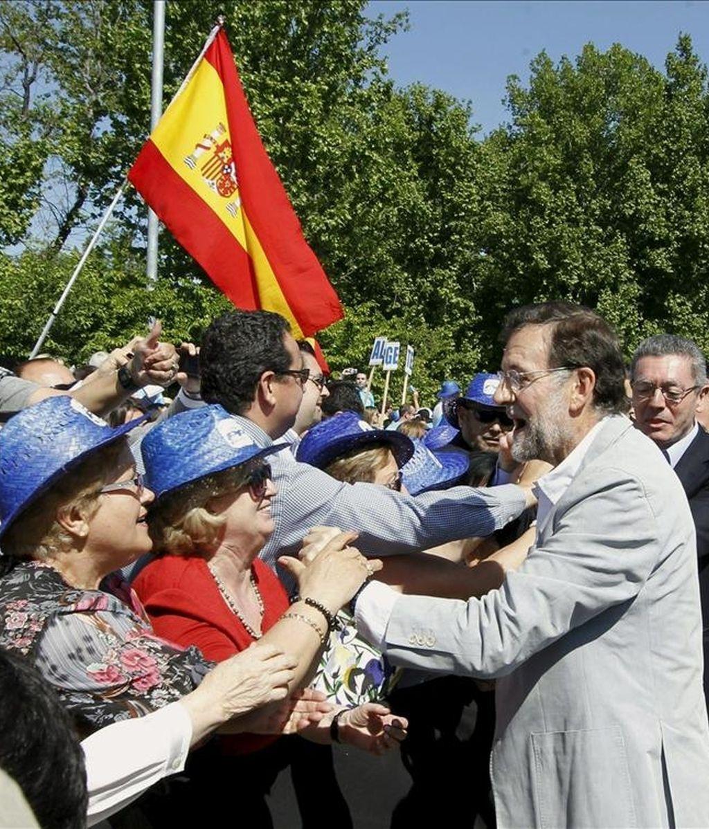 El presidente del PP, Mariano Rajoy (2d), y el alcalde de Madrid, Alberto Ruiz Gallardón (d), saludan a los asistentes a su llegada al acto principal de la jornada electoral del Partido Popular celebrado hoy en la explanada de Madrid Río. EFE