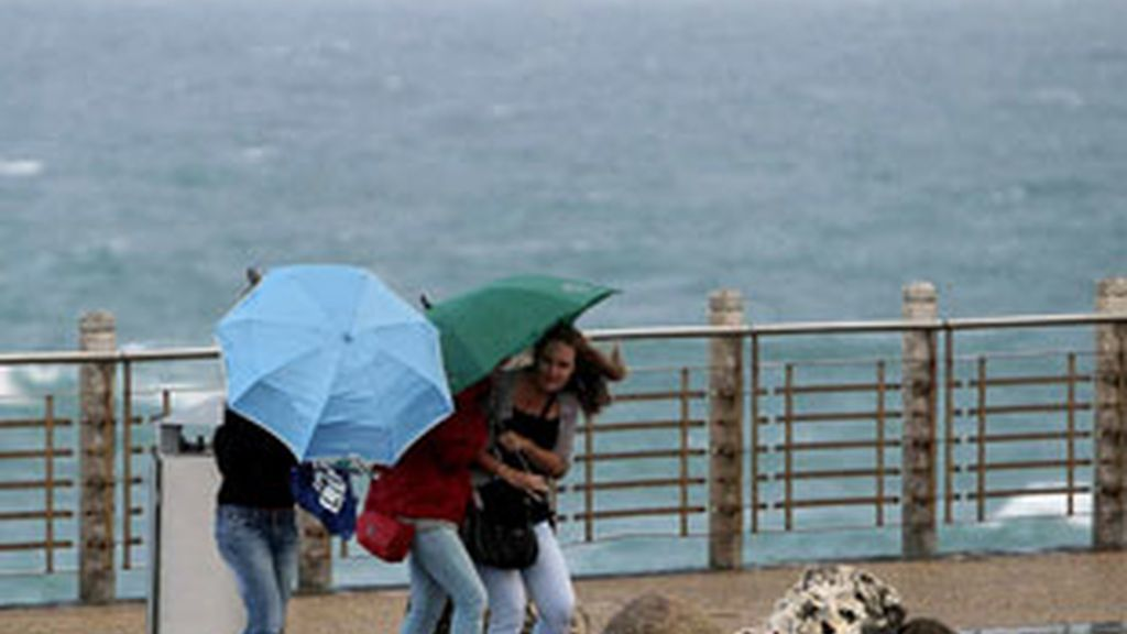 Tres turistas se protegen del fuerte viento y las precipitaciones en San Sebastián. Foto: EFE.