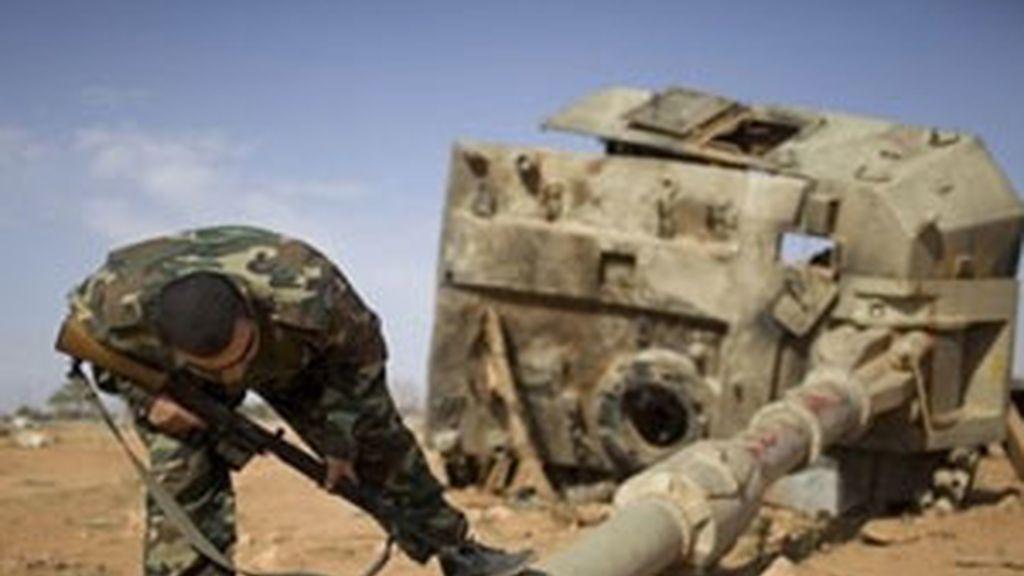 Un soldado rebelde examinan un tanque destruido de las fuerzas gadafistas. Foto: AP