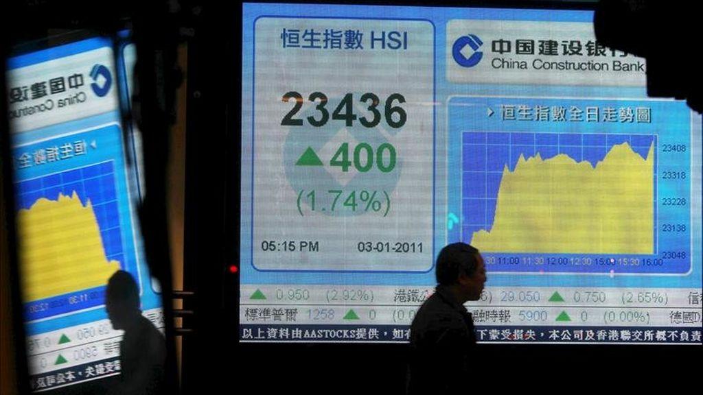 Un hombre camina junto a una pantalla informativa de los valores del índice Hang Seng en un banco en Hong Kong (China). EFE/Archivo