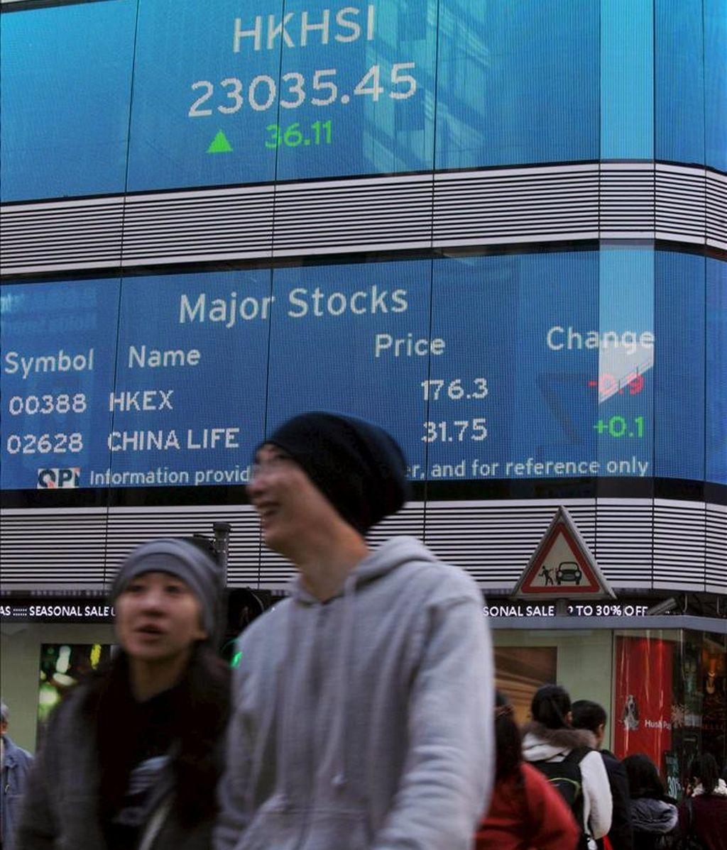 Peatones cruzan una calle en la que se ve una pantalla con información económica en un banco en Hong Kong (China). El mercado bursátil de Hong Kong abrió con una subida de 24,64 puntos en el índice Hang Seng. EFE/Archivo