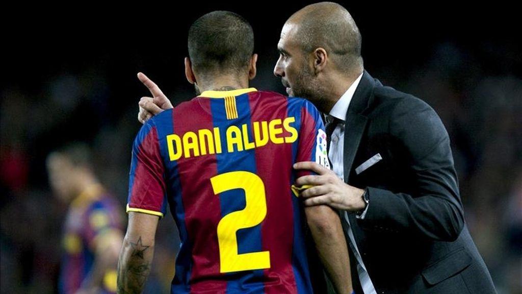 El entrenador del FC Barcelona Josep Guardiola (d) da instrucciones al defensa brasileño Daniel Alves durante el partido, correspondiente a la trigésima tercera jornada del Campeonato Nacional de Liga de Primera División, que el conjunto azulgrana disputó contra el Osasuna en el Camp Nou. EFE