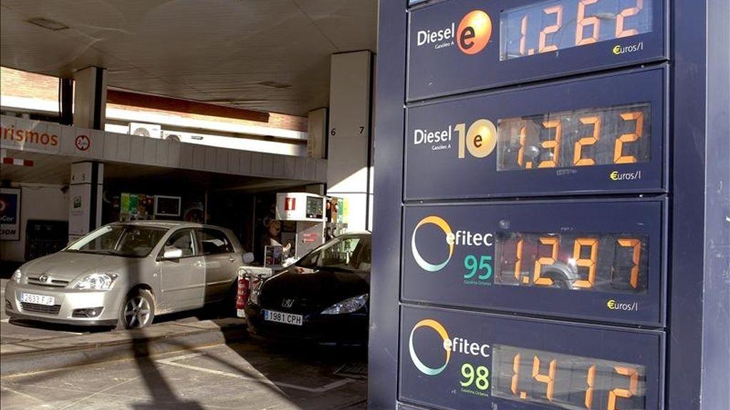 Varios vehículos repostan en una gasolinera de la capital junto a un panel que informa de los precios de los carburantes. EFE/Archivo