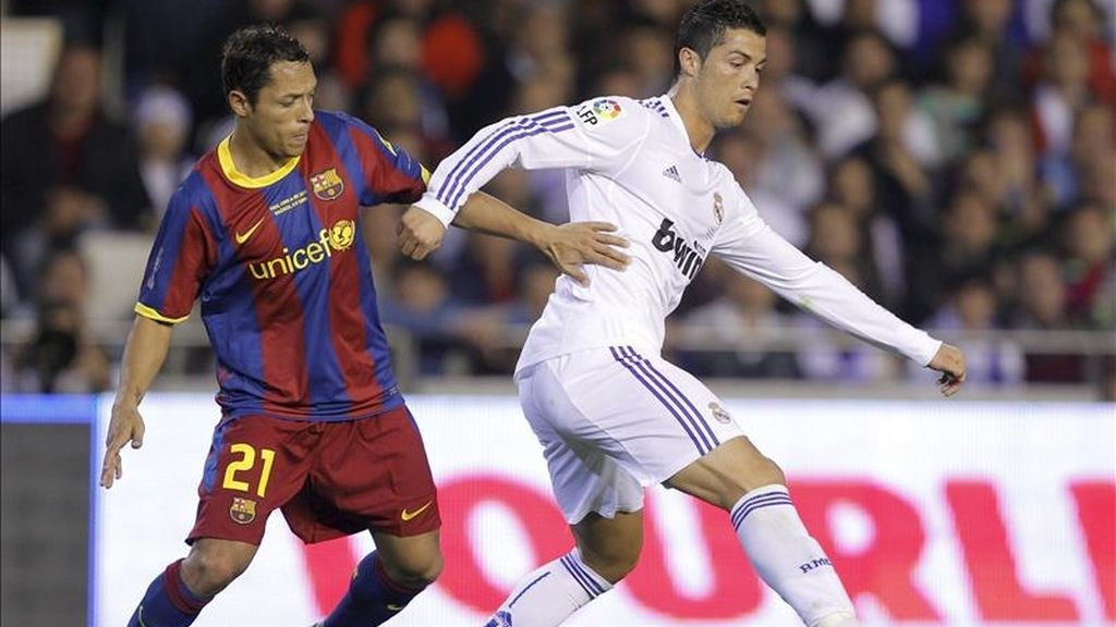 El delantero portugués del Real Madrid, Cristiano Ronaldo (d), controla el balón ante Adriano, defensa brasileño del FC Barcelona, durante el partido, correspondiente a la final de la Copa del Rey, que ambos equipos disputaron anoche en el estadio de Mestalla, en Valencia. EFE/Archivo