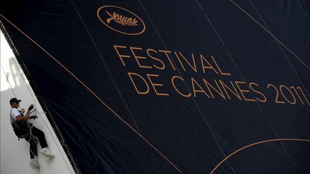 Un empleado trabaja en la colocación del póster oficial del 64 Festival de Cine de Cannes en la fachada del Palacio de Festivales, en Cannes (Francia. La ciudad francesa vive inmersa en los preparativos para el festival, que tendrá lugar entre el 11 y el 22 de mayo. EFE