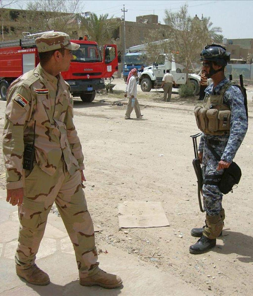 Policías iraquíes controlan el lugar donde se ha cometido un atentado con coche bomba, en Hila, Irak. EFE