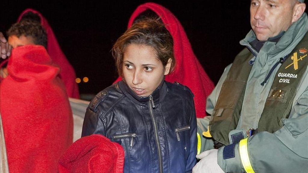 En la imagen, agentes de la Guardia Civil ayudan esta madrugada a desembarcar a los 31 inmigrantes de origen marroquí, dos de ellos mujeres, en el puerto granadino de Motril que el Servicio de la Guardia Civil y de Salvamento Marítimo, interceptaron en una embarcación a 8 millas al sur de la localidad de Castell de Ferro. EFE