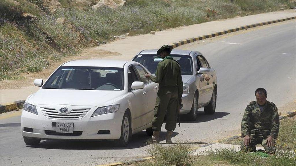 Un soldado libio de las fuerzas fieles al régimen del líder libio Muamar el-Gadafi inspecciona un coche mientras otro reza, en el punto de control de Gharyan, a unos 100 kilómetros al suroeste de Trípoli, Libia. EFE