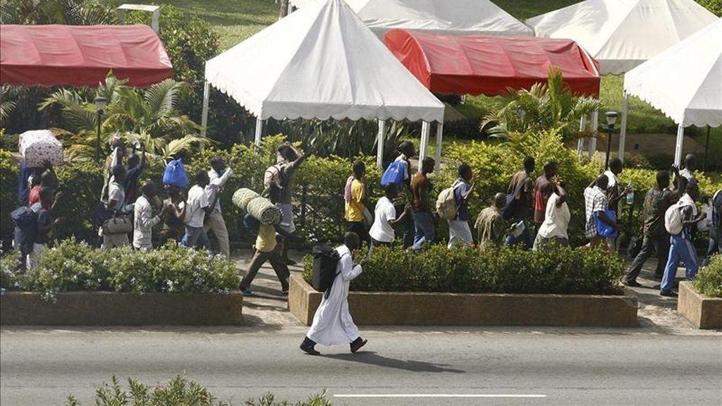Civiles costamarfileños abandonan el centro de la ciudad tras un bombardeo nocturno hoy, martes 5 de abril de 2011 en Abiyán (Costa de Marfil).  EFE