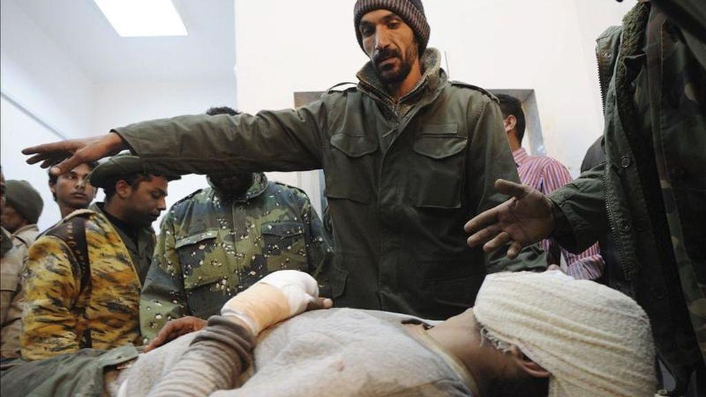 Rebeldes libios acompañan a un compañero que resultó herido en un bombardeo aéreo de la OTAN cerca de la ciudad de Brega, al este de Trípoli, en un hospital de Ajdabiya (Libia). EFE