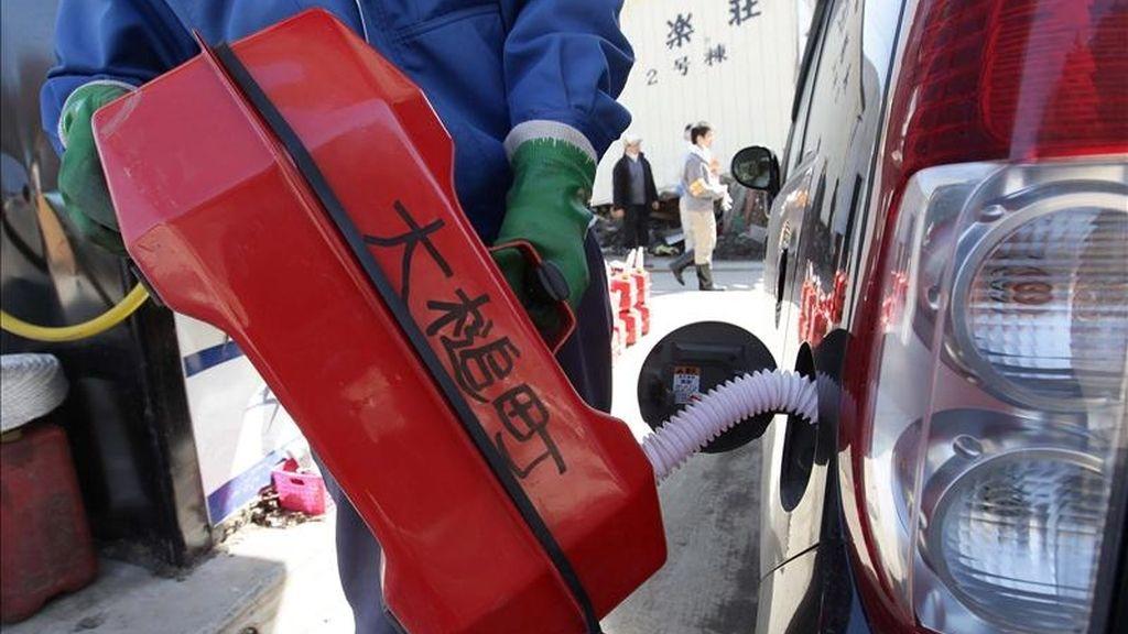 Un trabajador llena con combustible el depósito de un vehículo en Japón. EFE/Archivo