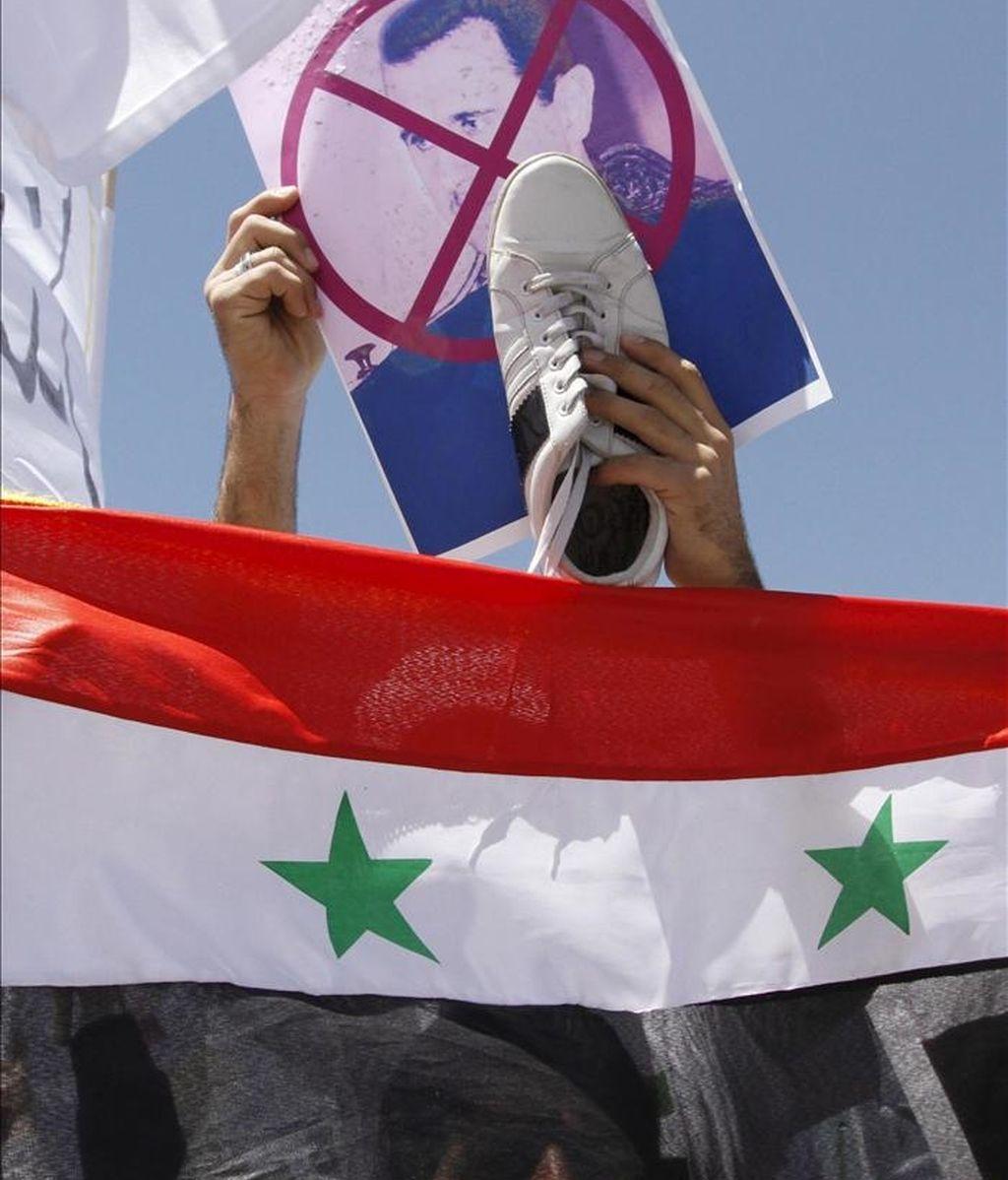 Un sirio residente en Jordania sostiene un retrato del presidente de Siria, Bachar al Asad, y un zapato sobre la bandera nacional durante una manifestación frente a la embajada siria en Amán hoy. EFE