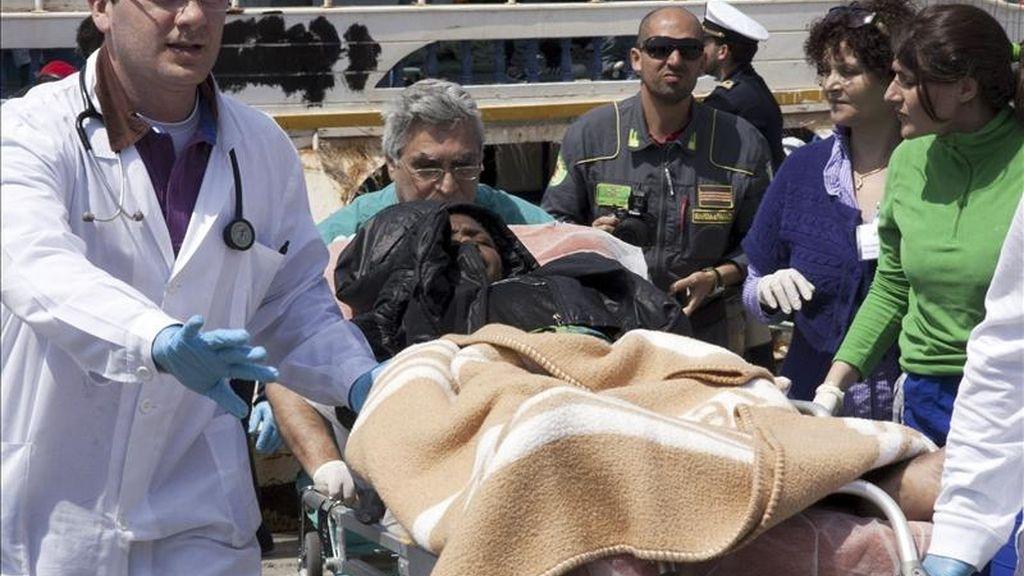 Médicos trasladan a una inmigrante en una camilla, tras llegar a la isla italiana de Lampedusa, procedente de Libia. EFE
