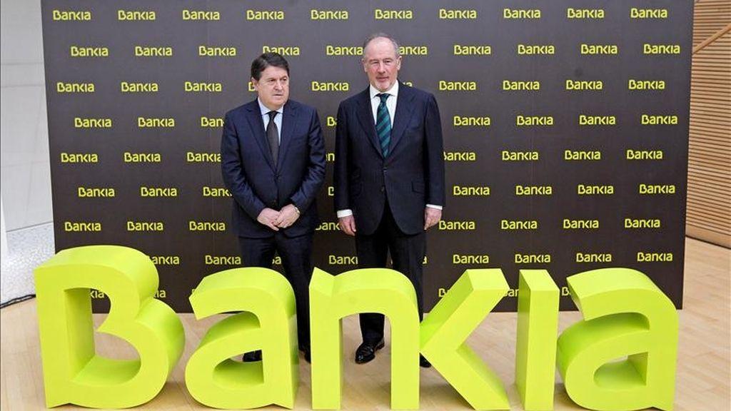 El presidente del hasta ahora llamado Banco Financiero y de Ahorros, Rodrigo Rato (d), posa junto al vicepresidente, José Luis Olivas (i), ante el nuevo nombre comercial del grupo, Bankia, escrito en color lima. EFE/Archivo