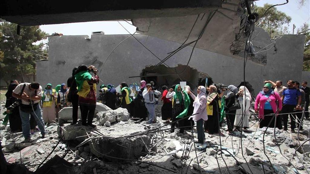 Periodistas y ciudadanos libios partidarios del líder libio, Muamar el Gadafi, se congregan junto a los restos de una de las residencias de la familia tras ser atacada durante un bombardeo de la OTAN, en Trípoli. EFE