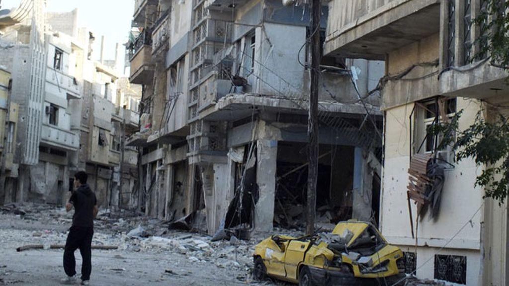 Un civil camina por la ciudad de Homs