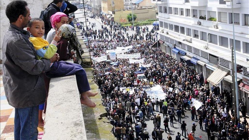 Varias personas observando el paso de una manifestación en petición de más democracia hoy en Casablanca (Marruecos). EFE