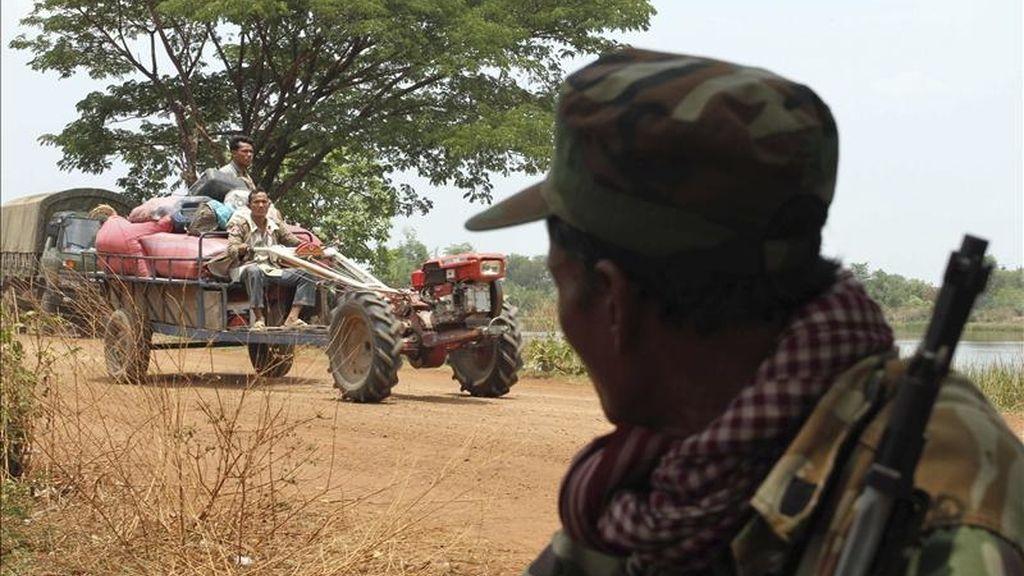 Un soldado camboyano observa ayer a varios civiles camboyanos que a bordo de un tractor se dirigen a lugar seguro tras abandonar su hogar para huir del conflicto en Banteay Ampil (Camboya). EFE