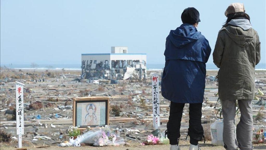 Residentes locales oran en un monumento budista hoy, 10 de abril de 2011, junto a los escombros de la devastación producida por el tsunami que destruyó a Natori (Japón). El número de muertos por el terremoto y el tsunami del 11 de marzo en el noreste de Japón se elevó a 12.985, al tiempo que otras 14.809 personas siguen desaparecidas, según el último recuento policial. EFE