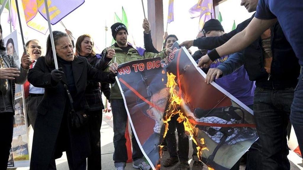 Imagen tomada el pasado 9 de marzo, en la que un grupo de manifestantes quema una fotografía del líder supremo iraní, el ayatolá Ali Jameini, durante un acto de protesta por la situación del campo de refugiados de Ashraf, en el noroeste de Irak, frente a la sede de las Naciones Unidas en Ginebra, Suiza. EFE/Archivo