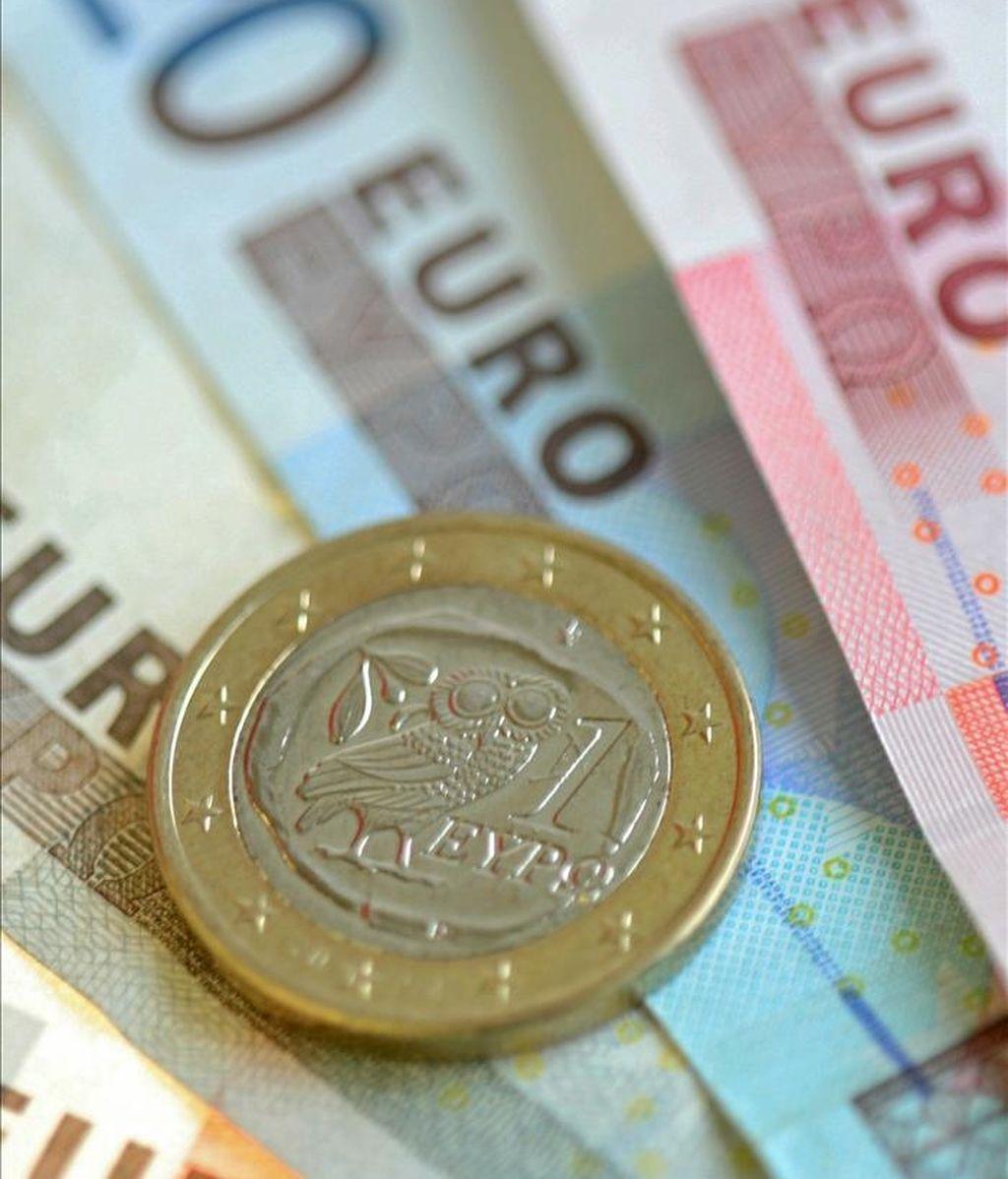 Una moneda griega de un euro sobre varios billetes de la misma divisa. EFE/Archivo