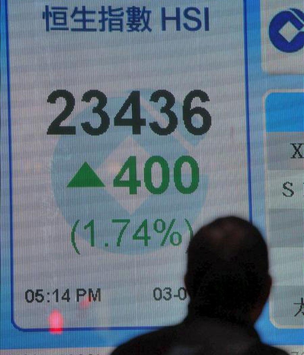 Un hombre camina junto a una pantalla informativa de los valores del índice Hang Seng. EFE/Archivo