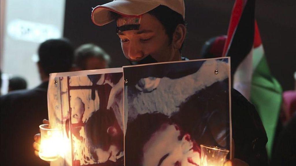 Un joven sirio residente en Jordania mostrando retratos de supuestas víctimas de la represión en Siria mientras participaba en una protesta convocada en los alrededores de la embajada de ese país en Amán este sábado. EFE