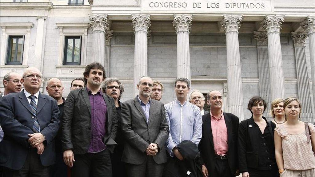Los portavoces de Bildu Óskar Matute (4 dcha) y Pello Urizar (2 izda), junto a los diputados de ERC Joan Tardá (3 izda) y Joan Ridao (4 izda), entre otros, durante la rueda de prensa que ofrecieron hoy a las puertas del Congreso, tras la decisión del presidente de la Cámara, José Bono, de prohibirla en el interior. EFE