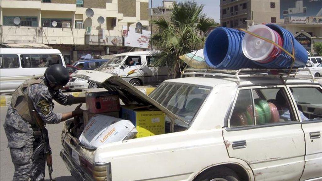 Un policía iraquí revisa el maletero de un vehículo en un punto de control en el centro de Bagdad. EFE/Archivo