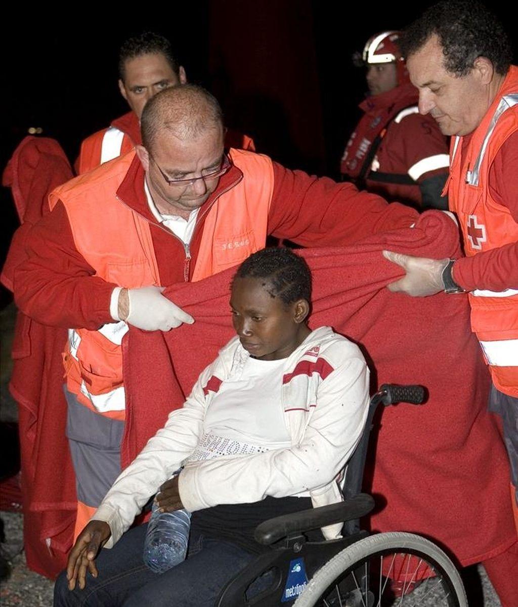 Miembros de Cruz Roja socorren a una mujer embarazada que llegó en febreroal puerto de Motril junto a otras 54 o 55 personas de origen subsahariano, entre ellos seis niños. EFE/Archivo