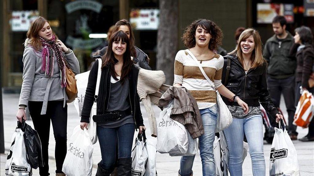 Un grupo de jóvenes camina con sus compras por la calle. EFE/Archivo