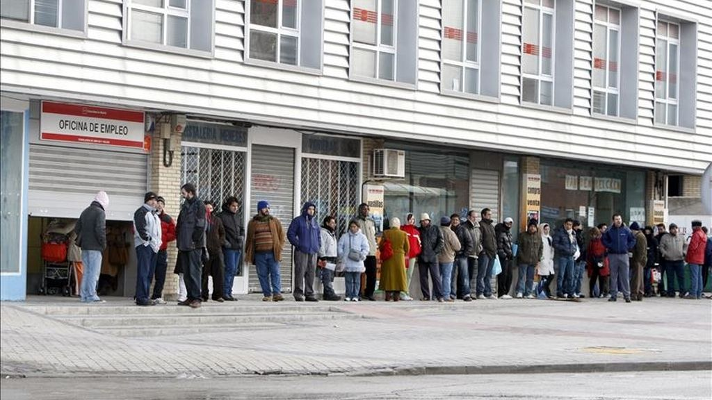 Varias personas forman una larga cola ante una oficina del INEM, en Madrid. EFE/Archivo
