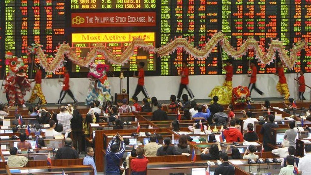 Filipinos representan la danza de un dragón y un león hoy, en la Bolsa de Manila (Filipinas). El corro bursátil abrió su sesión de negocios con danzas para celebrar el nuevo año chino, el año del conejo. EFE