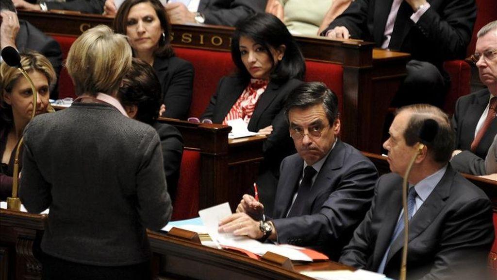 El primer ministro francés, François Fillon, (2d), conversa con la ministra de Exteriores, Michele Alliot-Marie, (i), durante una sesión plenaria en el parlamento francés, en París, Francia. EFE