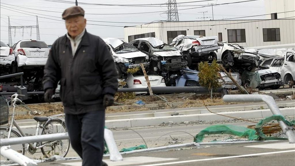Un anciano camina cerca de varios vehículos Toyota destinados a su exportación, y que fueron destruidos por el tsunami, en el puerto de Sendai, prefectura de Miyagi, en el noreste de Japón. EFE/Archivo