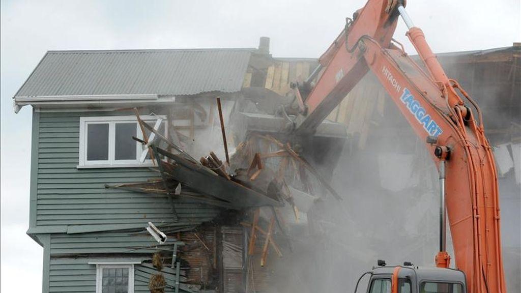 Una máquina derriba los restos de una casa dañada por el terremoto en Bealy Ave, Christchurch (Nueva Zelanda). EFE/Archivo