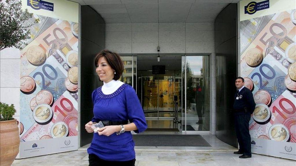 Una mujer camina entre dos vallas publicitarias con monedas y billetes de euro. EFE/Archivo