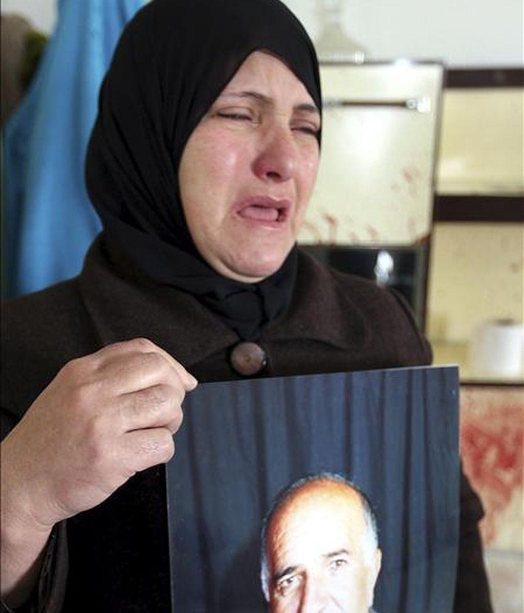La esposa de Omar Kawasme (67 años) sostiene su fotografía mientras que, en el fondo, se proyecta la cama manchada con sangre, donde fue asesinado por las tropas israelís durante un ataque para arrestar a presuntos milicianos, según alega su esposa hoy, 7 de enero de 2011, en Hebrón. EFE