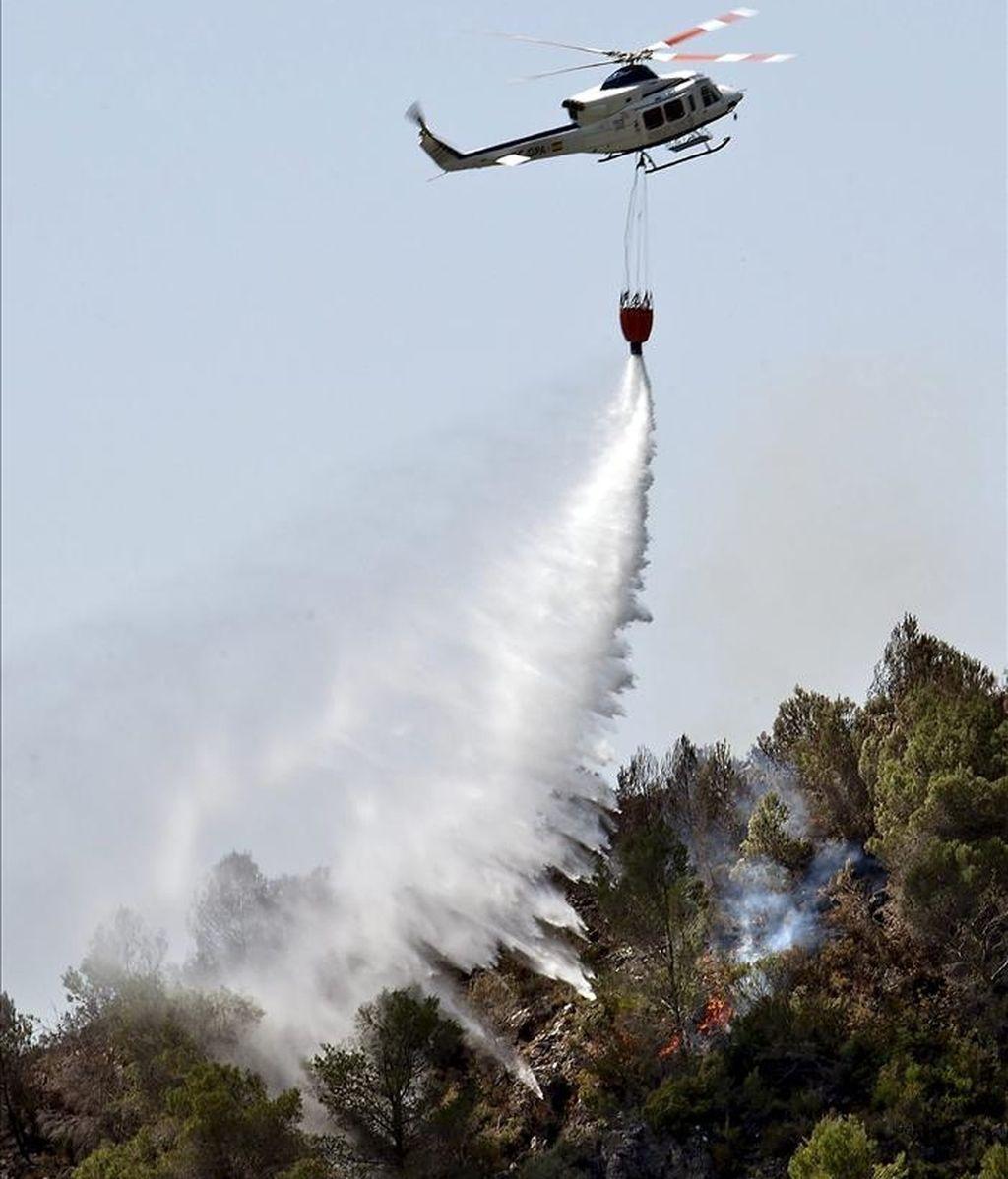 Un helicóptero arroja agua cerca de la población valenciana de Rótova tras el incendio declarado ayer en Benicolet, que anoche se dirigía hacia el paraje de Marxuquera y obligó al desalojo de varias viviendas. EFE