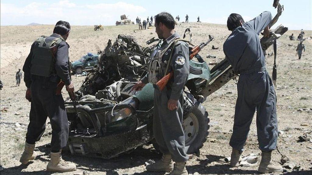 Oficiales de seguridad afganos inspeccionan la zona donde se ha producido un ataque con bomba contra un furgón policial en Pekara (Afganistán) hoy, 18 de abril de 2011. EFE